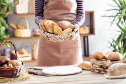 Female hands holding freshly bread in basket