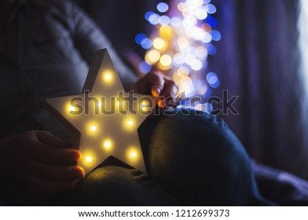 Female hands holding glowing white LED star with warm bokeh background indoor at home. Festive Christmas illumination, holiday atmosphere.
