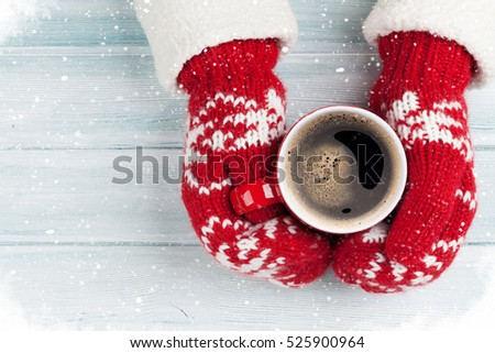 Female hands holding hot coffee above wooden table. Top view with copy space