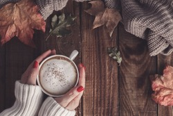 Female hands holding hot coffee cappuccino, blanket and autumn leaves on old wooden background. Vintage toning. autumn relax concept
