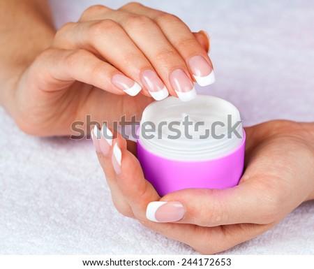 Female hands holding jar of cream