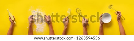 Female hands holding kitchen tools, sieve, rolling pin, bowl, sieve, brush, whisk, spatula for baking and cooking over yellow background. Food frame, bake concept with copy space. #1263594556
