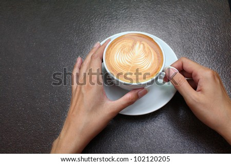 female hands holding Latte art, coffee cup.