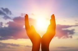Female hands holding lights of setting sun