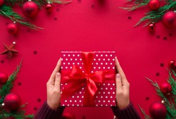 Female hands holding Merry Christmas gift box on red decorated festive background, woman prepare surprise new year winter merry handmade holiday present concept, flat lay, copy space, top view