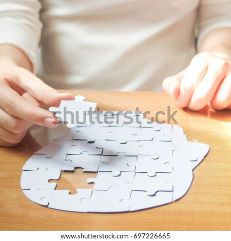 Female hands holding missing white jigsaw puzzle piece down into the place as a human head brain shape. Creative idea for memory loss, dementia, Alzheimer's disease and mental health concept. Square. #697226665