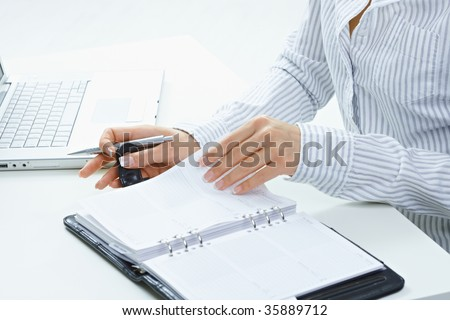 Female hands holding pen and turning a page of personal organizer.
