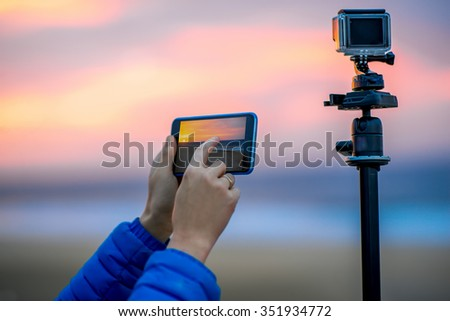 Female hands holding phone near the camera on the tripod. Remote control action camera filming time lapse video in the early morning