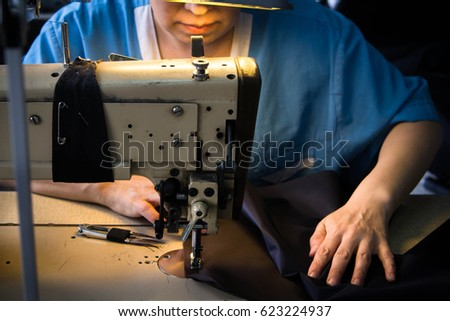 Female hands holding piece of cloth next to sewing machine on garment factory #623224937