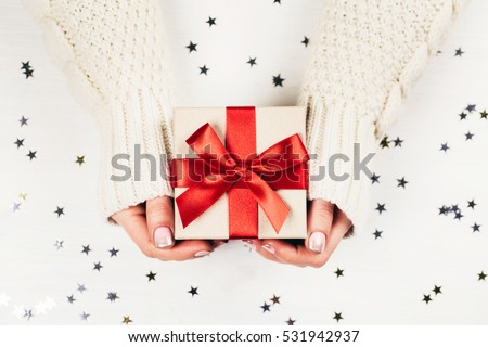 Female hands holding present with red bow on white rustic sparkling background. Festive backdrop for holidays: Birthday, Valentines day, Christmas, New Year. Flat lay