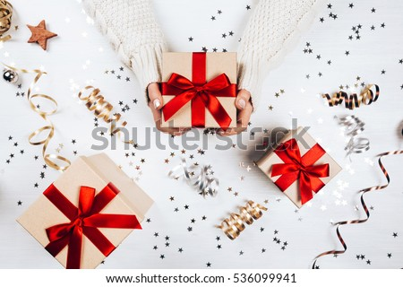 Female hands holding present with red bow on white rustic sparkling background. Festive backdrop for holidays: Birthday, Valentines day, Christmas, New Year. Flat lay style #536099941