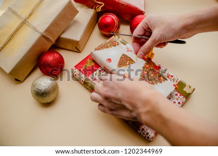 Female hands holding presents and packing presents. Presents and christmas balls, holiday concept. Red, green and golden paper.