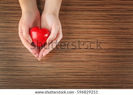 Female hands holding red heart on wooden background #596829251