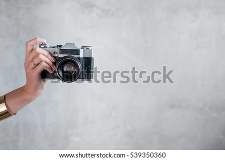 Female hands holding retro photo camera on the gray wall background #539350360