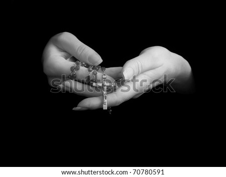 female hands holding rosary beads, isolated on black and toned to black & white