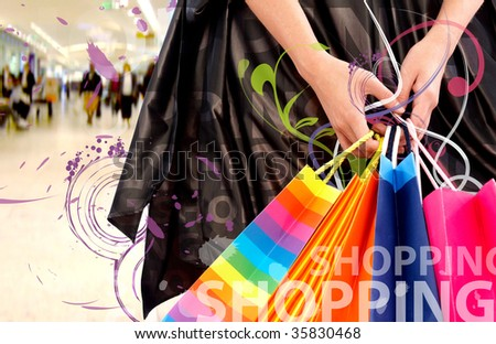 female hands holding shopping bags in a mall