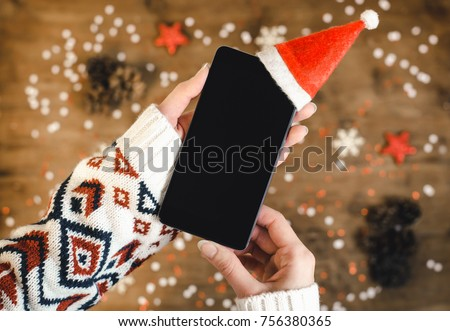 Female hands holding smart mobile phone with oled display on wooden background with Christmas gifts snowflakes and snow. Happy New Year, hat santa on mobile phone, Flat lay composition top view.