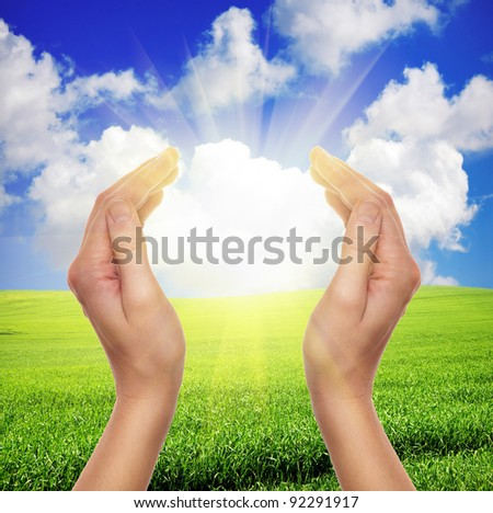 female hands holding sun over green field of grass and blue sky - religion and environment concept