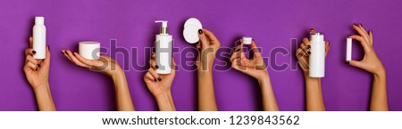 Female hands holding white cosmetics bottles - lotion, cream, serum on violet background. Banner. Skin care, pure beauty, body treatment concept. #1239843562