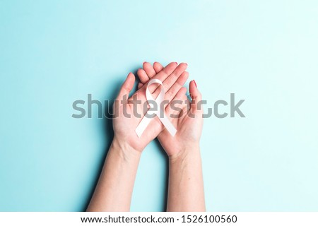 Female hands holding white ribbon on a blue background. November lung cancer awareness month.