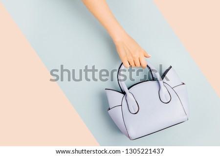 Female hands holds handbag on blue background . Flat lay, top view. Spring fashion concept in pastel colored