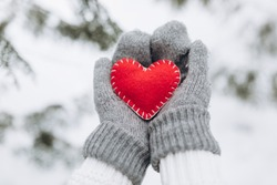 Female hands in a mittens holding red decorative heart for Valentine Day.