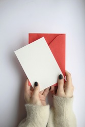 female hands in a sweater with manicure, holding a white sheet and a red envelope on a white background. postcard layout