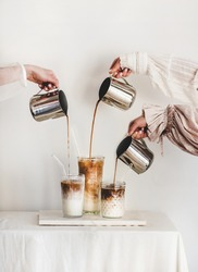 Female hands in elegant dress sleeves pouring fresh coffee to glasses with milk and making latte cappuccino drinks for breakfast on board over light wall background. Coffee beverage drinks