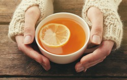 Female hands in mittens holding cup of tea on wooden background