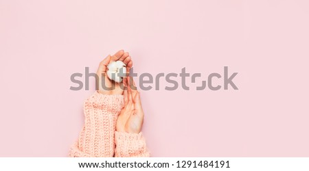 Female hands in pink knitted sweater hold a delicate cotton flower on pink pastel table top view. Flat lay. Copy space. Cotton flowers. Lifestyle gentle background #1291484191