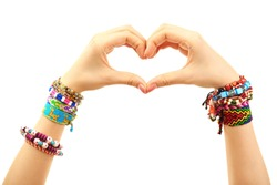 Female hands in shape of heart with bracelets isolated on white