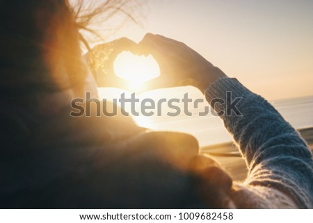 Female hands in the form of heart against sunlight at sunset on the Baltic sea #1009682458
