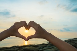 Female hands in the form of heart against sunlight in sunrise sky on beach morning time. Hands in shape of love heart, Love concept.