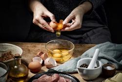 female hands is braking eggs for making schnitzel