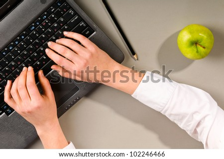 female hands is working on modern laptop, view from above