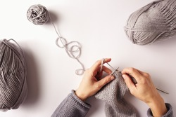 Female hands knitting with gray wool,  top view