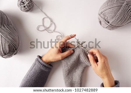 Female hands knitting with gray wool, top view #1027482889