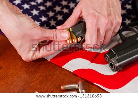 female hands loading a hand gun with hallow point bullets and an american flag in the background