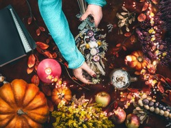 Female hands make autumn dried flowers arrangement on dark work space with pumpkins, fall leaves, burning candles, apples, fairy lights with bokeh and  books. Top view. Flat lay. Cozy autumn home