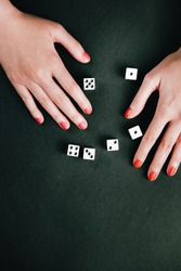 Female hands making a number sequence with rolling dices. White square dices against a dark green background.