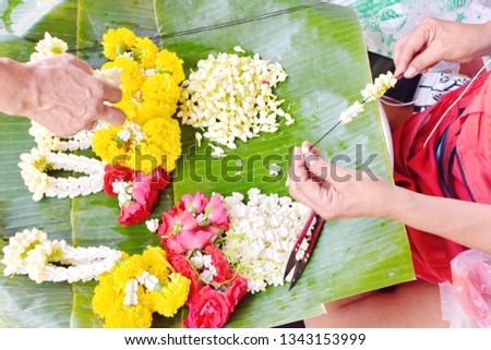Female hands making Thai traditional garland (Phuang Malai) selling for Songkran festival or Thai New Year, row beautiful garlands, jasmine, rose, marigold fresh flowers on banana leaf, overhead view #1343153999