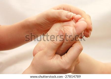 Female hands massage a children foot