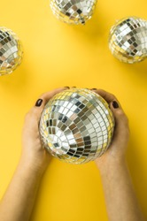 Female hands neatly hold Christmas toy in the form of disco mirror ball on bright yellow background. View from above. Flat lay. Place for text. Copyspace.