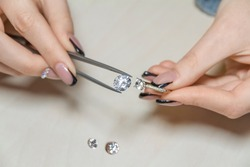 female hands of a jeweler are holding a gem. diamond luxury ring close up.diamond stones appraiser. jewelry quality check.manufacture of precious stones. inspection of artificial diamond