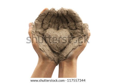 Female hands on a white background holding a heart made out of clay - stock photo