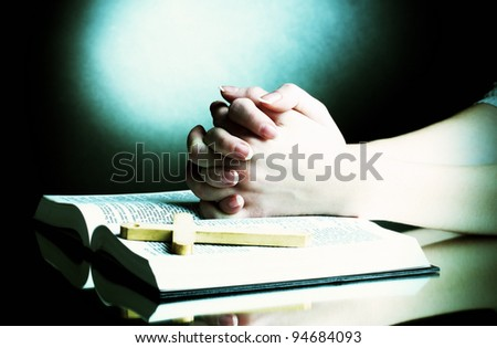 Female hands on open russian holy bible on black backround