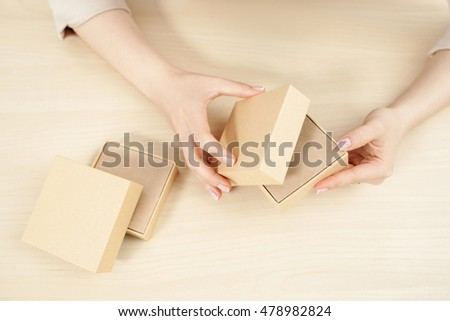 Female hands opening carton box, flat lay. Top view on woman holding and unblocking package with some product, free space. Delivery service. online shopping, parcel getting concept #478982824