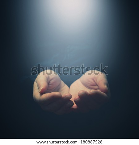 Female hands opening to light. Holding, giving, showing concept. Selective focus on fingers.