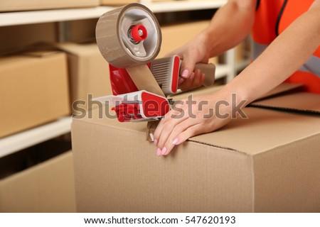 Female hands packing box at warehouse, closeup