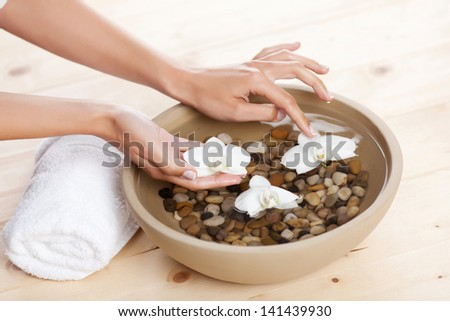 Female hands placing white orchids onto a bowl with pebbles filled with water so that they float on the surface in a spa treatment concept